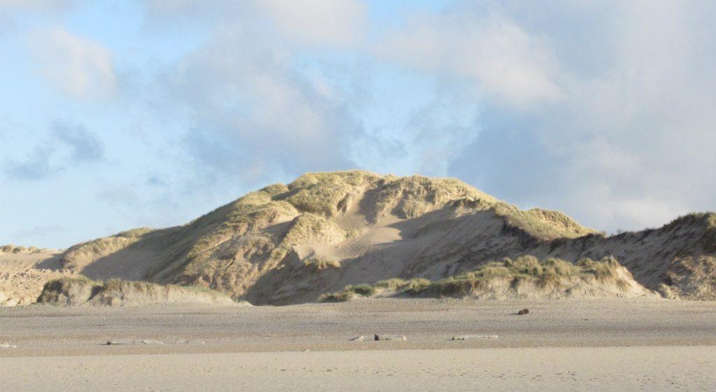 Au-delà de la plage, la dune blanche se détache contre le ciel nuageux. Ses monts irréguliers forment des dénivelés où l'ombre s'installe. Ailleurs, le sable resplendit sous le soleil ...