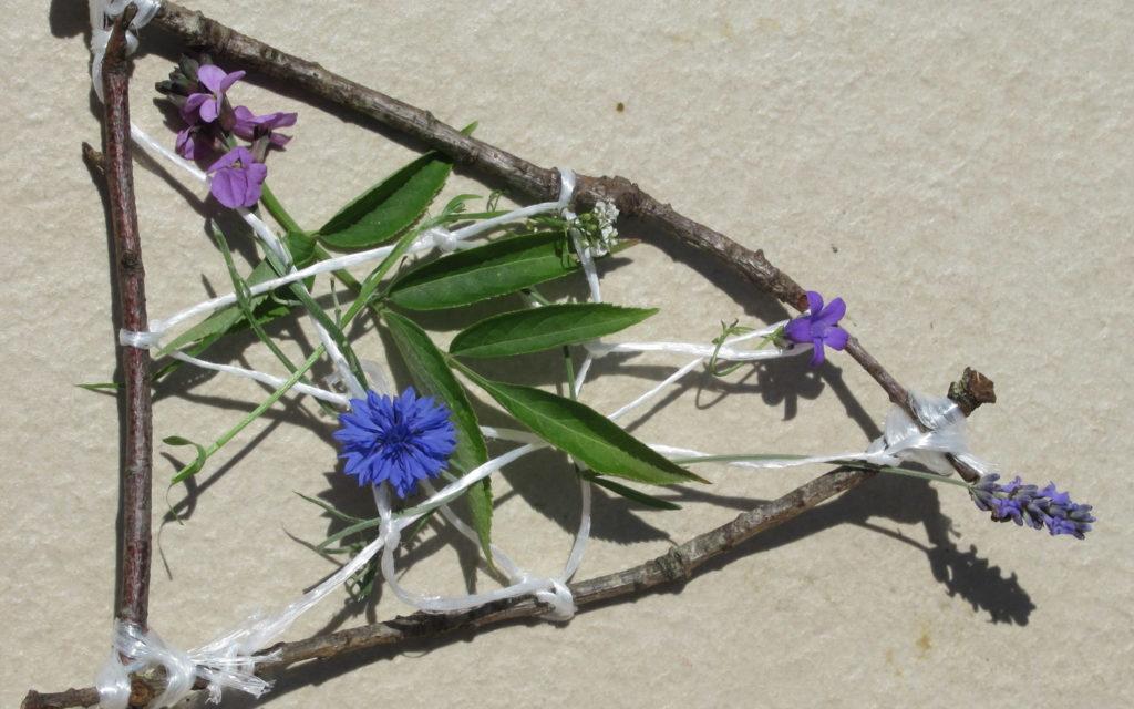 Un petit tissage réalisé à partir de branches, de ficelles et de fleurs violettes et bleues.